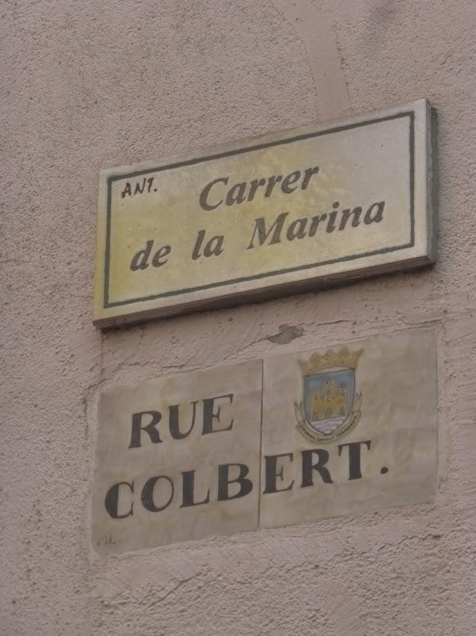 O idioma catalão ainda é observado na cidade, como nessa placa, convivendo com outra em francês...
