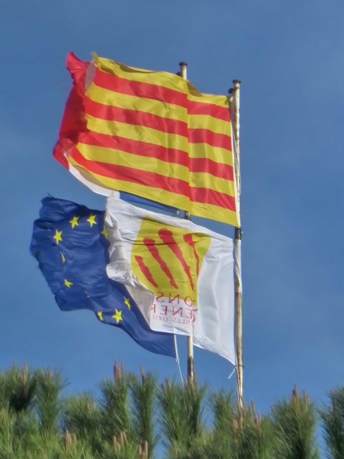 Bandeiras da Catalunha (sobreposta à da França), da União Europeia e uma quarta não identificada: tremulam juntas no alto do Château Royal