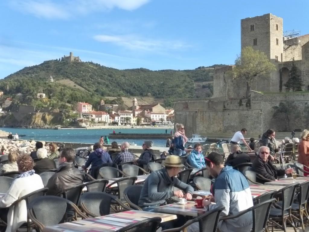 Turistas sentados em cafés a beira mar, com parte das montanhas que cercam Collioure