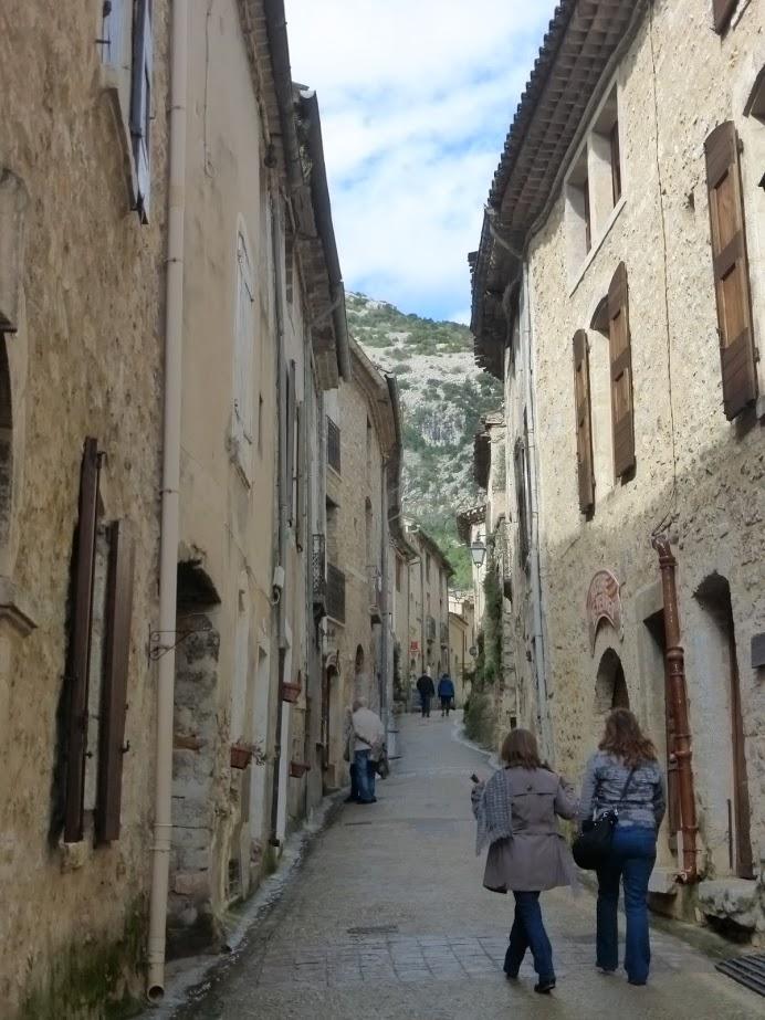 Turistas caminham em ruela de Saint-Guilhem-le-Désert: cidade com apenas 200 habitantes