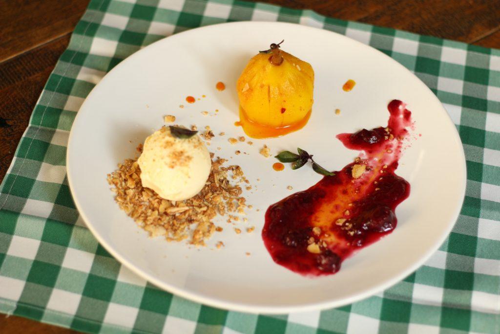 Pêra ao vinho branco e açafrão: pêra cozida ao vinho branco e açafrão, acompanhado de sorvete de pistache e farofa de amêndoas com calda de frutas vermelhas